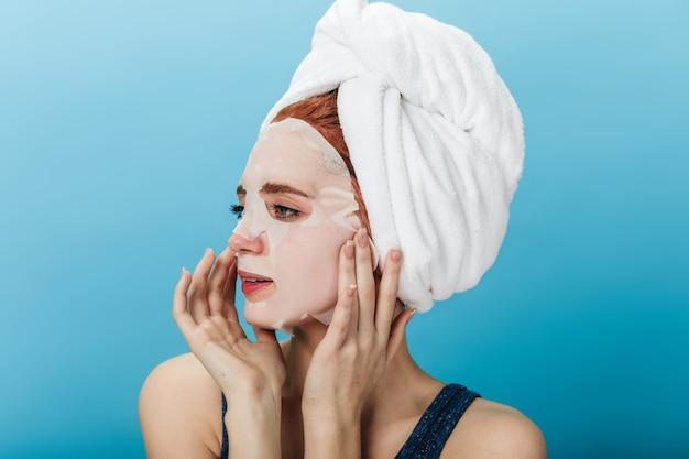 Verträumtes mädchen, das gesichtsmaske lokalisiert auf blauem hintergrund anwendet. studioaufnahme der jungen dame mit handtuch auf dem kopf weg schauend.