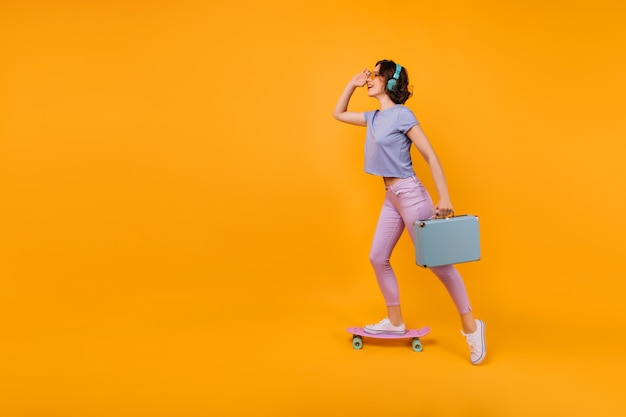 Verträumtes mädchen in der rosa hose, die auf skateboard steht und musik hört. inspiriertes lockiges weibliches modell in kopfhörern, die mit blauem koffer posieren.