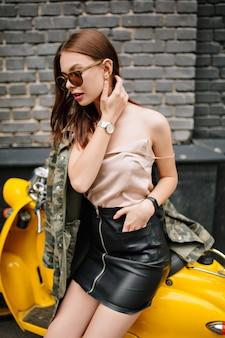 Verträumtes mädchen mit glattem braunem haar in der armbanduhr, die weg schaut, während sie auf gelbem moped sitzt