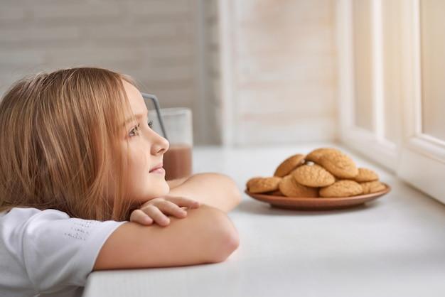 Verträumtes mädchen mit keksen auf fensterbank