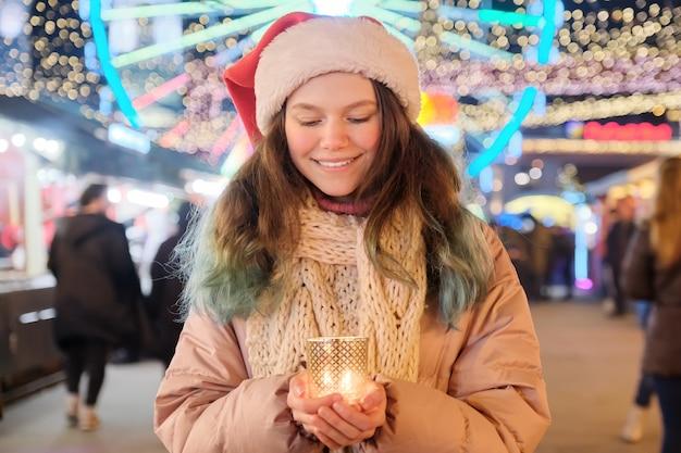 Verträumtes schönes jugendlich mädchen im weihnachtsmannhut mit brennender kerze. mädchen am weihnachtsmarkt
