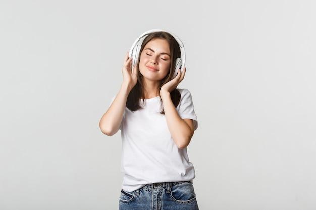Verträumtes schönes mädchen, das musik in drahtlosen kopfhörern genießt und glücklich lächelt.