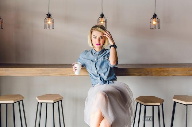 Verträumtes stilvolles mädchen mit blonden haaren und rosa lippen, die in einem café mit holzstühlen und tisch sitzen. sie hält eine tasse kaffee und berührt ihre haare