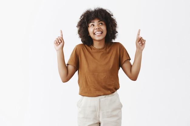 Verträumtes und kreatives attraktives dunkelhäutiges weibliches model mit afro-frisur im trendigen outfit, das mit freudigem amüsiertem lächeln auf einen interessanten kopierraum blickt und nach oben zeigt