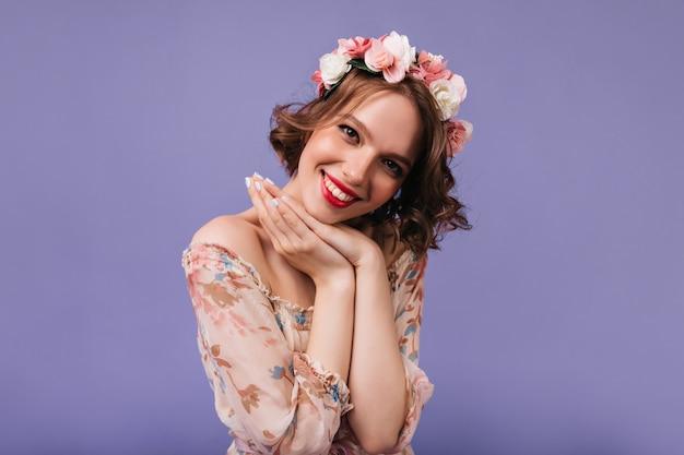 Verträumtes weibliches modell mit dem schönen lächeln, das aufwirft. hübsches lockiges mädchen mit rosen im haar.