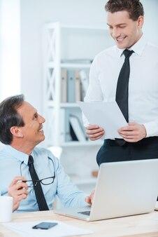 Vertrag besprechen. lächelnder reifer geschäftsmann, der an seinem arbeitsplatz sitzt