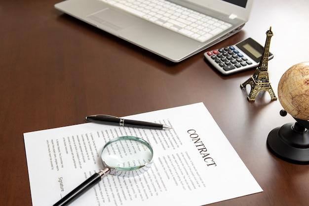 Vertragsdokumente und vergrößerungsgläser auf dem schreibtisch eines geschäftsmannes.