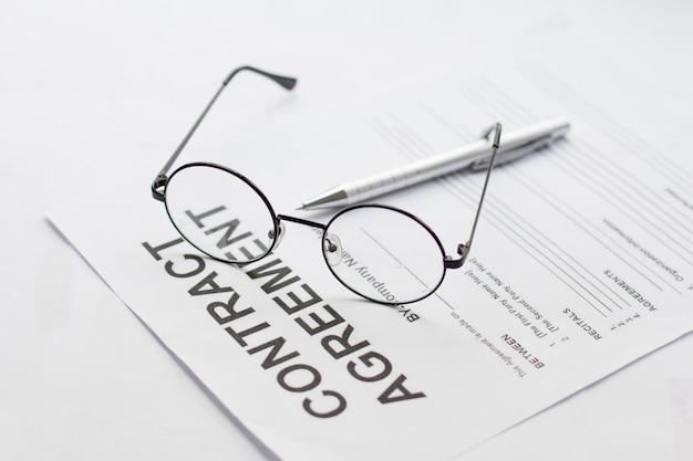 Vertragsunterzeichnung mit brille und stift in der nähe