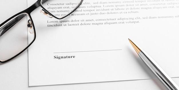 Vertragsunterzeichnung mit stift und brille