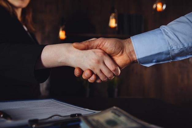 Vertragsunterzeichnungskonzept. mann und frau vereinbaren und nehmen geld.
