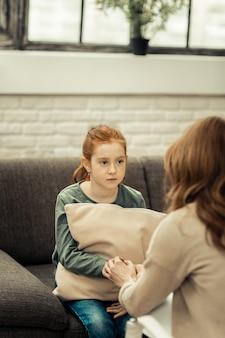 Vertrauen entwickeln. freudloses junges mädchen, das ihrem therapeuten gegenüber sitzt, während sie ihr die hand gibt