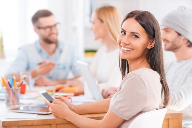 Vertrauen in ihr team. schöne junge frau, die über die schulter schaut und lächelt, während sie das handy hält und zusammen mit seinen kollegen am holztisch im büro sitzt