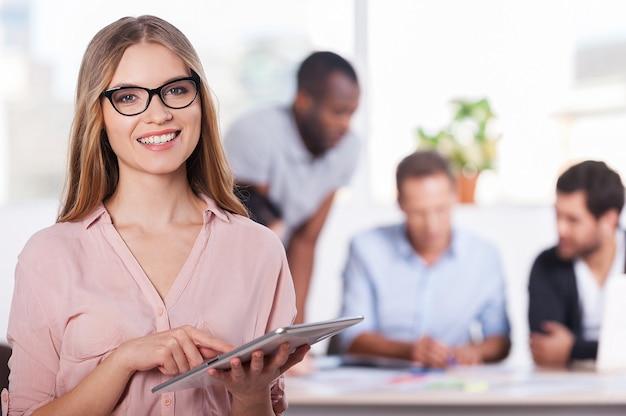 Vertrauen in ihr team. selbstbewusste junge frau mit brille, die an einem digitalen tablet arbeitet und lächelt, während drei leute am hintergrund arbeiten
