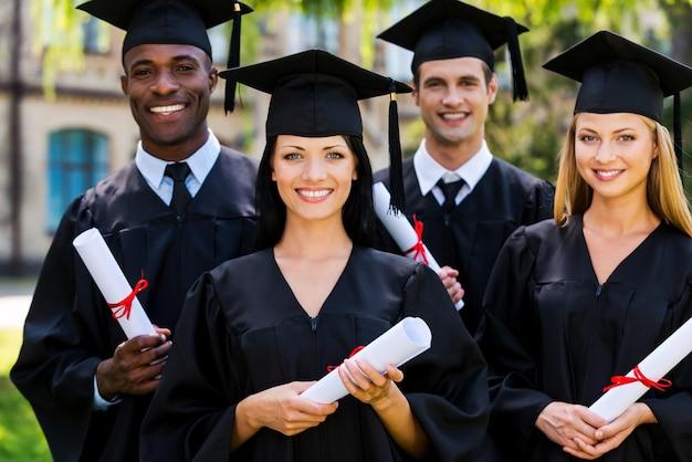 Vertrauen in ihre zukunft. vier hochschulabsolventen in abschlusskleidern stehen dicht beieinander und lächeln