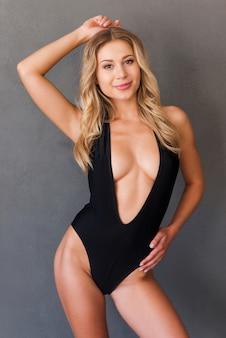 Vertrauen in ihren perfekten körper. attraktive junge frau mit blonden haaren in schwarzer badebekleidung, die vor grauem hintergrund posiert