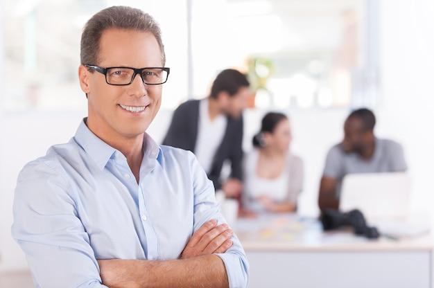 Vertrauen in sein team. selbstbewusster reifer mann mit brille, der die arme verschränkt hält und lächelt, während drei leute am hintergrund arbeiten