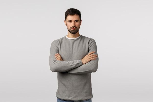 Vertrauen, mut und motivation konzept. ernst aussehender hübscher starker ernster bärtiger mann in grauer strickjacke, professionell und entschlossen aussehen, arme über der brust kreuzen, durchsetzungsfähige bereitschaftshaltung