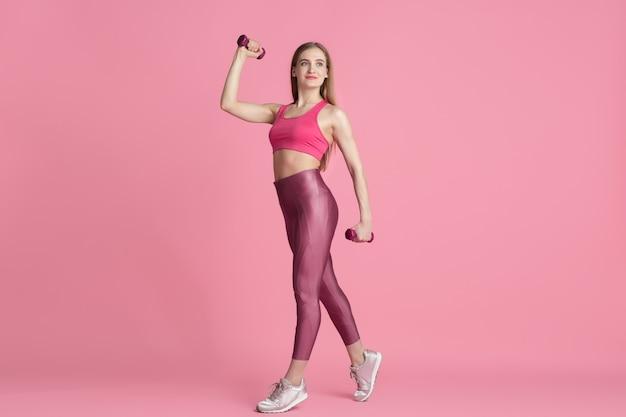Vertrauen. schöne junge sportlerin üben, einfarbiges rosa porträt. kaukasisches modell der sportlichen passform mit gewichten. bodybuilding, gesunder lebensstil, schönheits- und aktionskonzept.