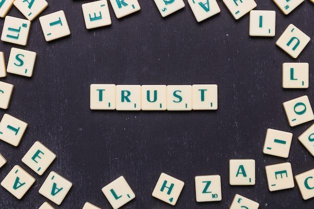 Vertrauen sie das wort, das auf dem schwarzen hintergrund vereinbart wird, der durch scrabblebuchstaben umgeben wird