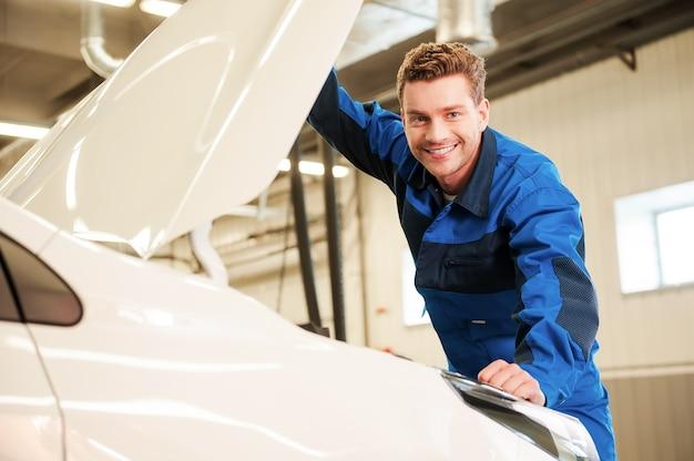 Vertrauen sie profis. hübscher junger mann in uniform, der auto untersucht und lächelt, während er in der werkstatt steht