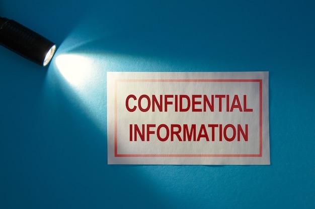Vertrauliche informationen - inschrift auf einer weißen karte im lichtstrahl