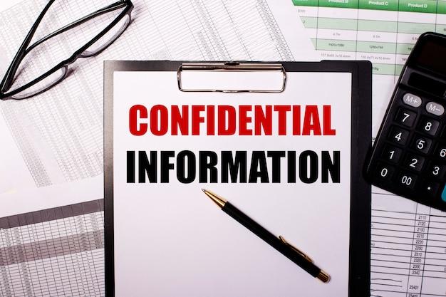 Vertrauliche informationen werden auf ein weißes blatt papier in der nähe der brille und des taschenrechners geschrieben.
