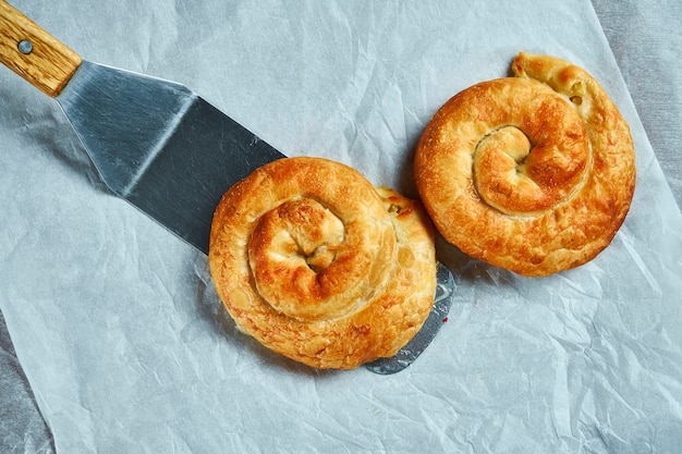 Vertuta - aus abgasteig mit apfel auf weißem pergamentpapier rollen. leckeres und delikates gebäck der moldauischen und ukrainischen küche. draufsicht
