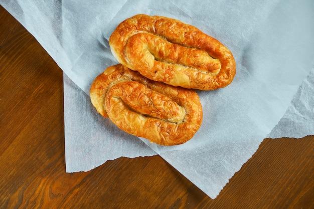 Vertuta - aus auspuffteig mit kohl auf weißem pergamentpapier rollen. leckeres und delikates gebäck der moldauischen und ukrainischen küche. draufsicht