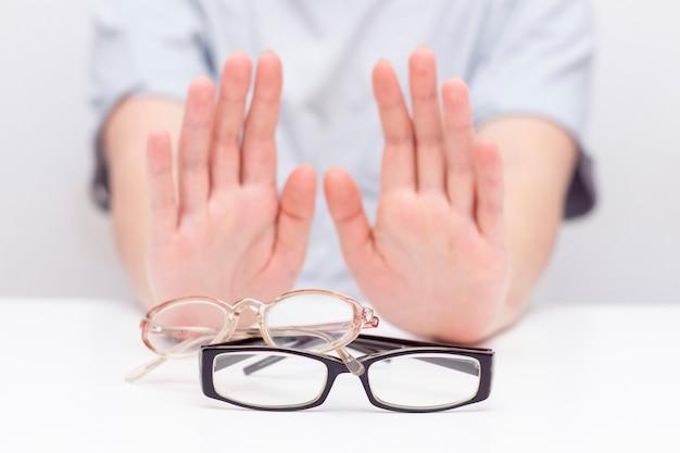Verweigerung der sehkraft. hände lehnen gläser ab.