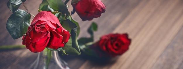 Verwelkte rose auf dunkelgrauem hintergrund und holztisch mit herbstblättern und blättern, designkonzept der traurigen valentinstagsromantik, aufgebrochen, kopie, raum.