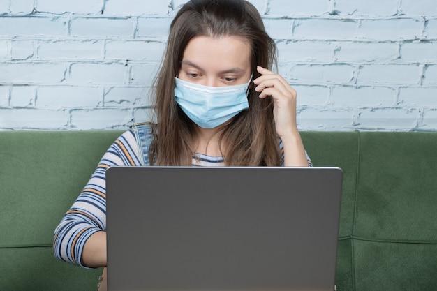 Verwenden der gesichtsmaske bei der arbeit mit einem laptop im büro