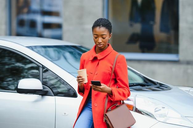 Verwenden des smartphones während des wartens. frau auf der ladestation der elektroautos am tag. brandneues fahrzeug.