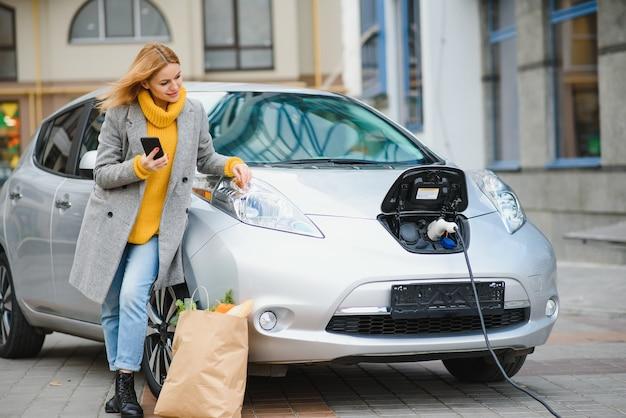 Verwenden des smartphones während des wartens. frau auf der ladestation der elektroautos am tag