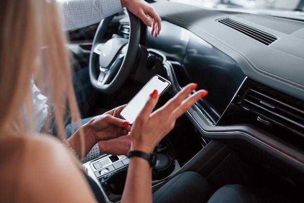Verwenden des telefons zum suchen einer richtung. positiver manager, der der kundin die merkmale des neuen autos zeigt