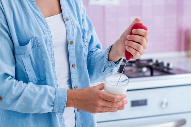 Verwenden eines milchaufschäumers für die zubereitung von aromatischem cappuccino in der küche zu hause