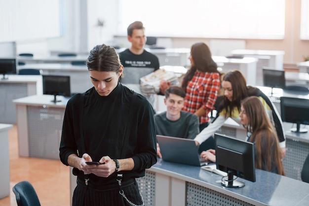Verwenden eines schwarzen smartphones. gruppe junger leute in freizeitkleidung, die im modernen büro arbeiten