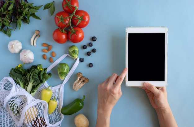 Verwenden sie das digitale tablet von hand mit der öko-tasche und frischem gemüse. online-anwendung zum einkaufen von lebensmitteln und produkten für biobauern. lebensmittel- und kochrezept oder ernährungszählung.