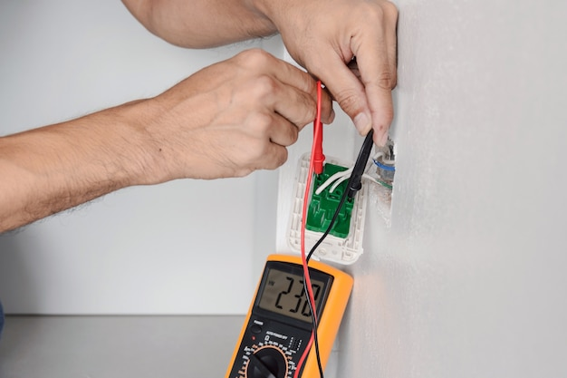 Verwenden sie ein digitales messgerät, um die spannung an der steckdose an der wand zu messen.