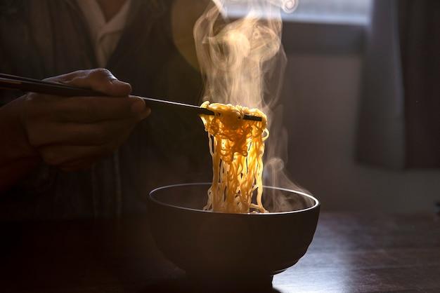 Verwenden sie essstäbchen, um nudeln zu handhaben. in einem topf mit rauch auf einem asiatischen ofen