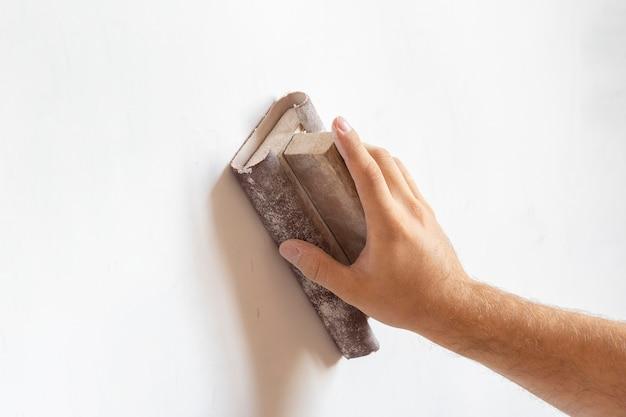 Verwenden sie sandpapier, um die wandoberfläche zu schleifen. oberflächennivellierung, arbeiten im haus. platz kopieren.