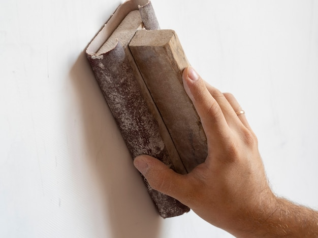 Verwenden sie sandpapier, um die wandoberfläche zu schleifen. oberflächennivellierung, arbeiten im haus.