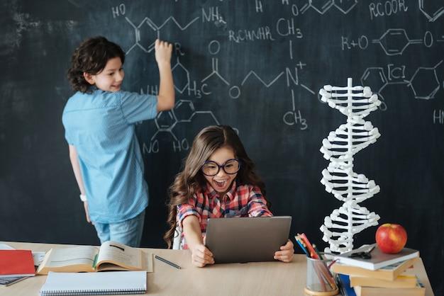 Verwendung moderner geräte für die bildung. freudige kluge kleine schüler, die in der schule sitzen und chemieunterricht genießen, während sie notizen machen und tablette benutzen