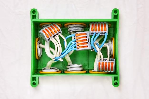 Verwendung von anschlussklemmen mit druckhebel bei der installation einer rechteckigen kunststoff-anschlussdose.