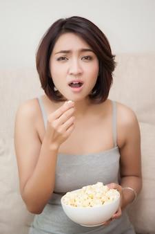 Verwirren sie die schönen frauen, die popcorn essen