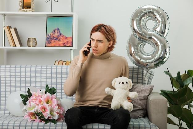 Verwirrt aussehender, gutaussehender kerl am glücklichen frauentag, der teddybären hält, spricht am telefon, das auf dem sofa im wohnzimmer sitzt