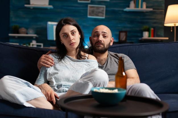 Verwirrt erstauntes junges paar, das dokumentarfilme mit schockiertem gesichtsausdruck anschaut, popcorn isst, das auf der couch sitzt. konzentrierte erwachsene, die bis spät in die nacht fernsehen und ihre freizeit genießen