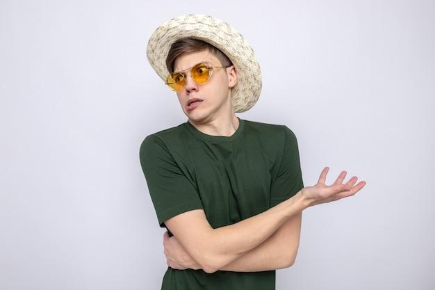 Verwirrt hält die hand an der seite junger gutaussehender kerl mit brille mit hut