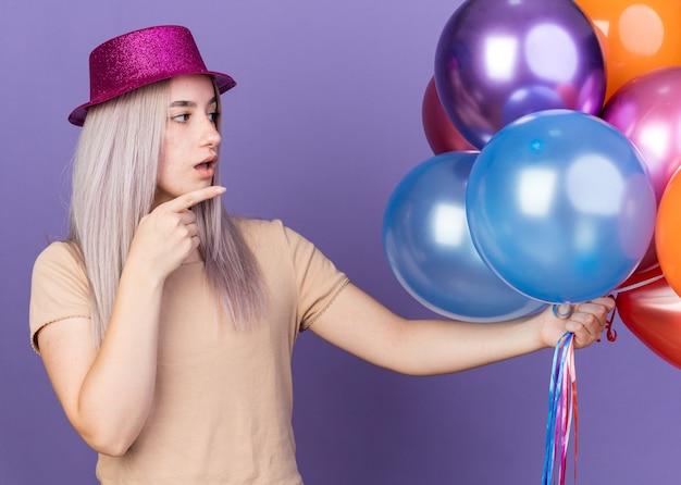 Verwirrt junges schönes mädchen mit partyhut hält und zeigt auf ballons