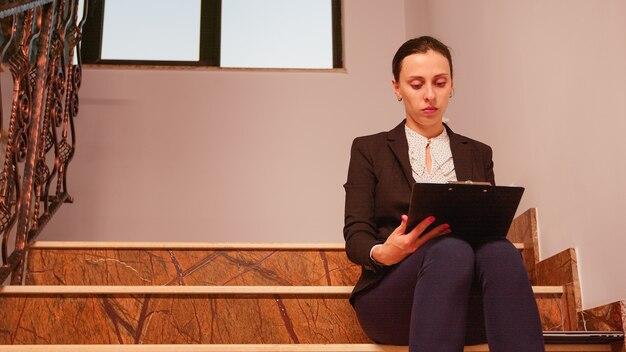 Verwirrt überarbeitete geschäftsfrau, die an einer schwierigen unternehmensfrist arbeitet, die auf der treppe sitzt und die zwischenablage hält. unternehmer, der überstunden bei der arbeit macht, während kollegen das bürogebäude verlassen.