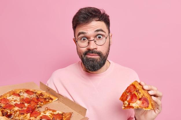 Verwirrt überraschter unrasierter junger mann isst leckere pizza hat fast-food-sucht genießt leckeren snack in der pizzeria sieht verwundert aus, posiert gegen rosa wand. ungesundes ernährungskonzept Premium Fotos